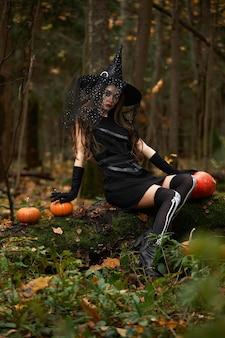 Mujer joven en vestido negro con sombrero de bruja y calabaza naranja colocados en el bosque, concepto de halloween