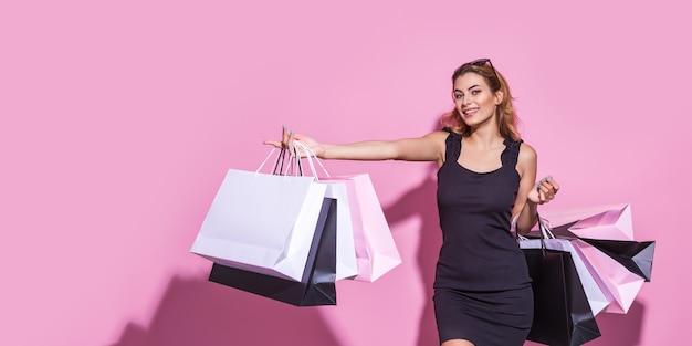 Mujer joven con un vestido negro sostiene bolsas de la compra y apuntando con el dedo al espacio vacío en un fondo rosa ...