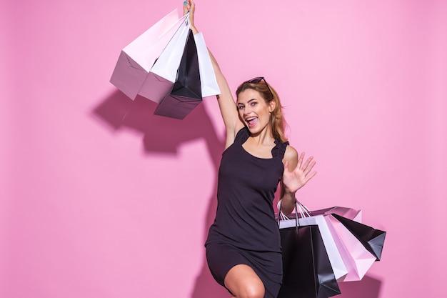 Mujer joven con un vestido negro sostiene bolsas de la compra y emocionalmente levantó las manos sobre un fondo rosa