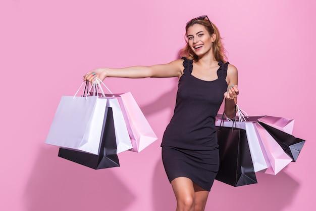 Mujer joven con un vestido negro tiene bolsas de la compra sobre un fondo de color rosa