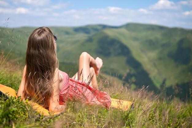 Mujer joven en vestido rojo acostado en la pradera de hierba verde en un día cálido y soleado en las montañas de verano disfrutando de la vista de la naturaleza.
