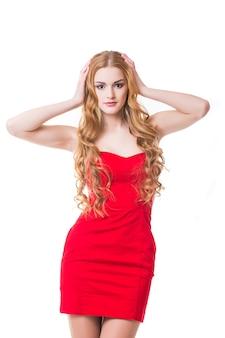 Mujer joven en vestido rojo bailando sobre fondo blanco.