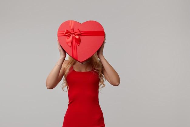 Una mujer joven en un vestido rojo con una caja roja en forma de corazón cerca de su rostro. día de san valentín y 8 de marzo