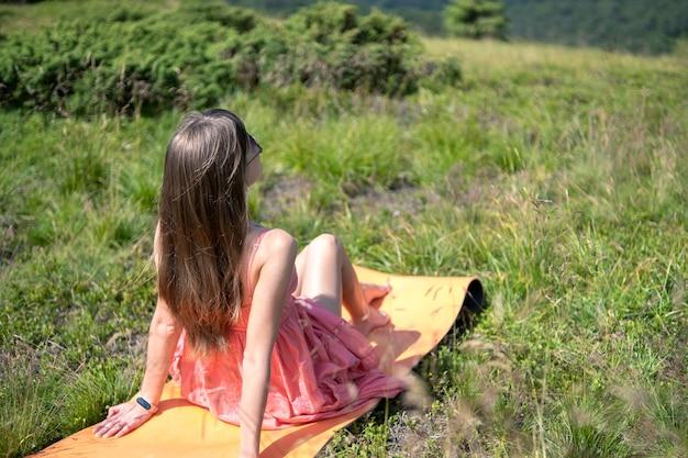 Mujer joven en vestido rojo descansando sobre el campo de hierba verde en un día soleado en las montañas de verano disfrutando de la vista de la naturaleza.
