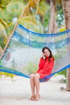 Mujer joven en vestido rojo disfrutando de un día soleado en la hamaca