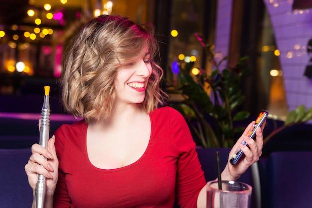 Mujer joven en el vestido rojo fuma una cachimba en el bar de cachimba y charlando con amigos.