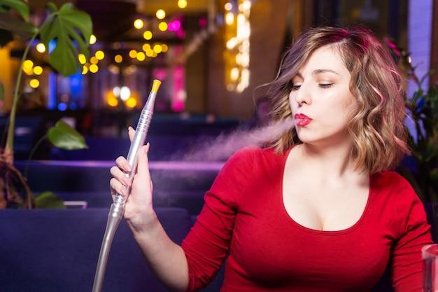 La mujer joven en el vestido rojo fuma una cachimba en el bar de la cachimba.