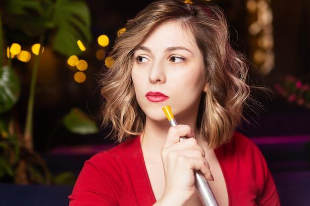 La mujer joven en el vestido rojo fuma un primer hookan. la discoteca o el bar shisha fuman.