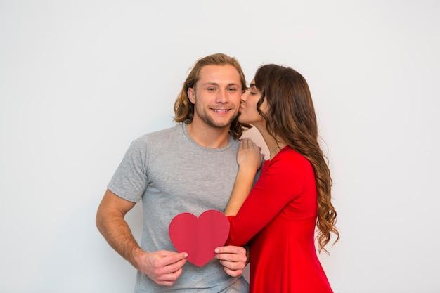 Mujer joven en vestido rojo que besa a su novio que sostiene el papel rojo de la forma del corazón contra el fondo blanco