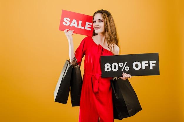 Mujer joven en vestido rojo con venta 80% signo y bolsas de papel aisladas sobre amarillo
