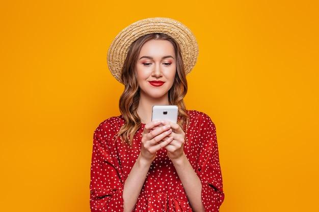Mujer joven en un vestido rojo de verano sombrero de paja charlando por teléfono móvil aislado sobre la pared de la pared de color naranja. pedidos en línea compras concepto de crédito comercial.