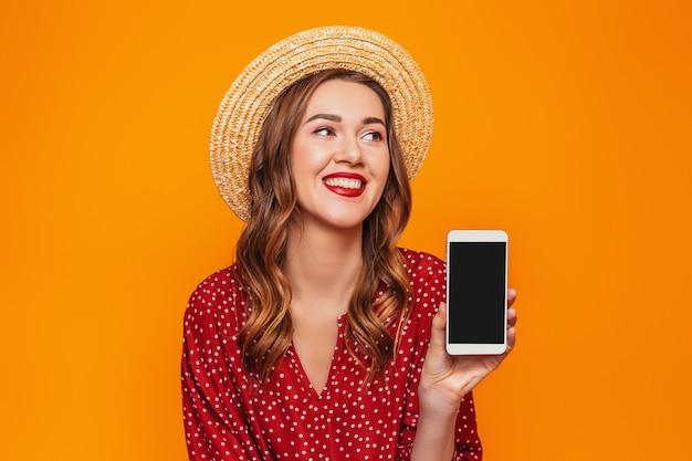 Una mujer joven en un vestido rojo de verano con sombrero de paja sostiene un teléfono móvil y lo muestra a la cámara con una pantalla negra vacía y mira el espacio de la maqueta para el diseño de la pared naranja