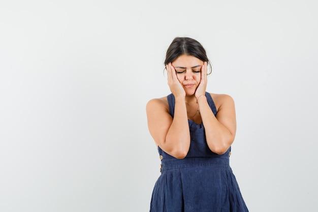 Mujer joven en vestido sosteniendo las palmas de las manos en las mejillas y mirando fatigado
