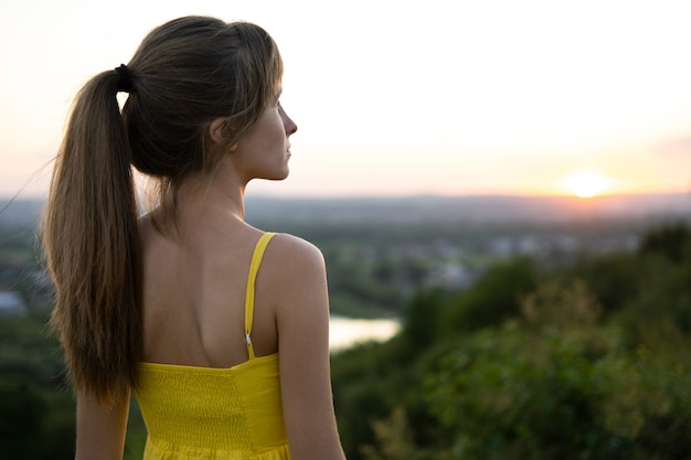 Mujer joven en vestido de verano de pie al aire libre disfrutando de un día cálido.