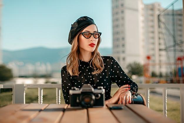 Una mujer joven con un vestido vintage de lunares negros con una vieja cámara en sus manos posando en la calle