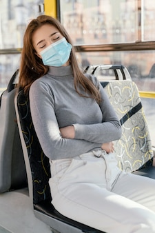 Mujer joven viajando en autobús urbano con mascarilla quirúrgica