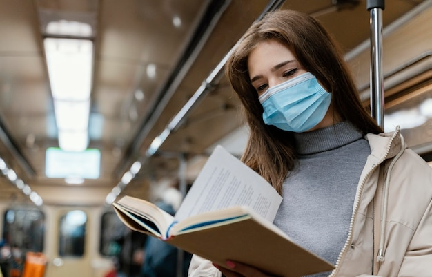Mujer joven viajando en metro leyendo un libro
