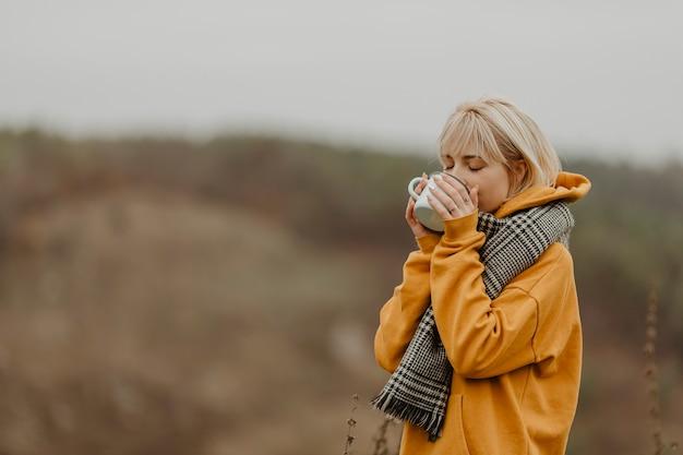 Mujer joven en viaje de invierno bebiendo té