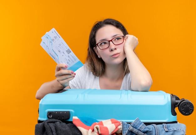 Mujer joven viajera en camiseta blanca con maleta llena de ropa y boletos de avión con la cabeza inclinada en la mano mirando a un lado con expresión pensativa en la cara de pie