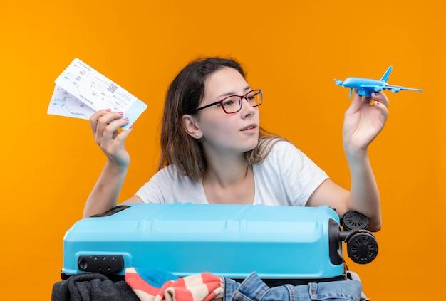 Mujer joven viajera en camiseta blanca de pie con maleta llena de ropa con billetes de avión y avión de juguete mirándolo con interés sobre la pared naranja