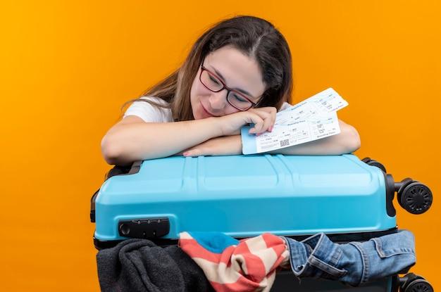 Mujer joven viajera en camiseta blanca de pie con maleta llena de ropa sosteniendo boletos de avión con la cabeza inclinada en la maleta durmiendo sobre la pared naranja