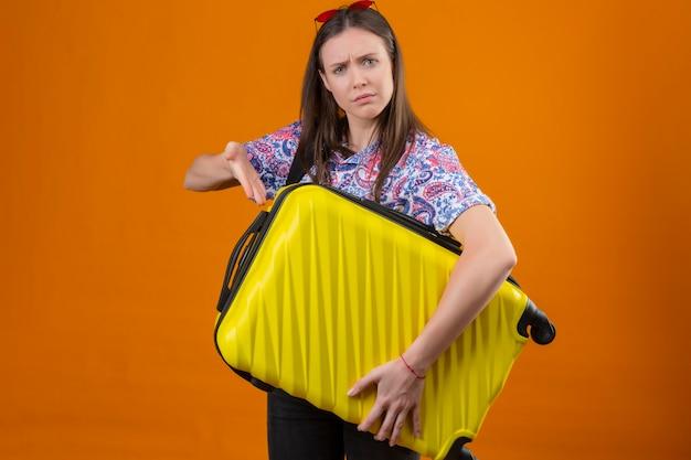 Mujer joven viajera disgustada con gafas de sol rojas en la cabeza de pie con mochila sosteniendo la maleta apuntando con el brazo de la mano hacia ella con el ceño fruncido