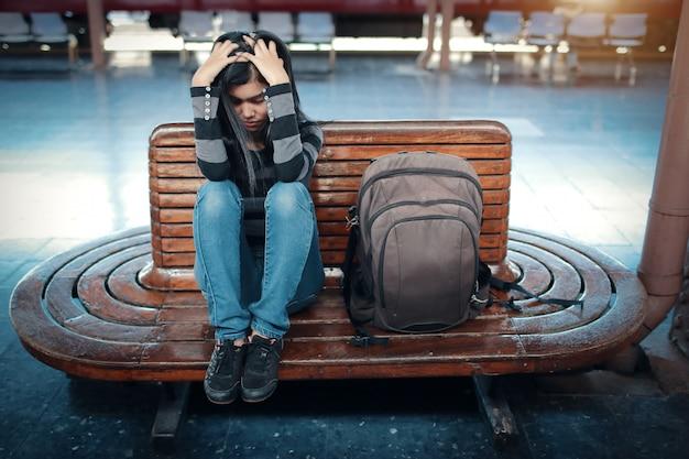 Mujer joven viajera con mochila deprimida y estresada mientras espera el tren