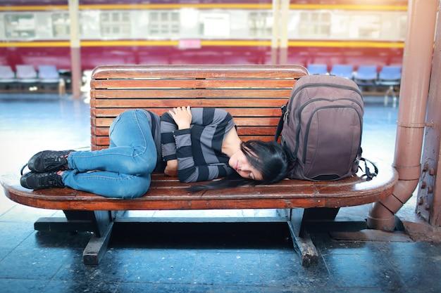 Mujer joven viajera con mochila durmiendo y esperando el tren.