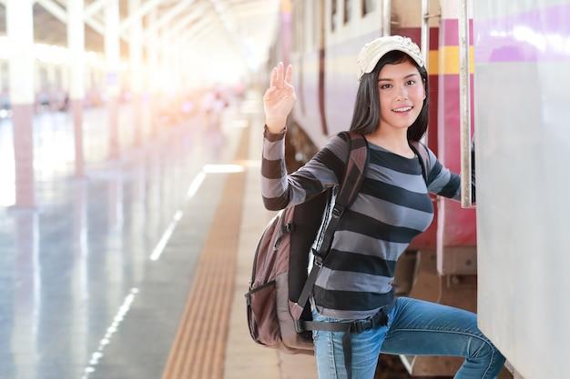 Mujer joven viajera con mochila subiendo al tren.
