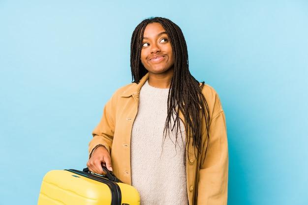 Mujer joven viajero afroamericano sosteniendo una maleta aislada soñando con lograr objetivos y propósitos