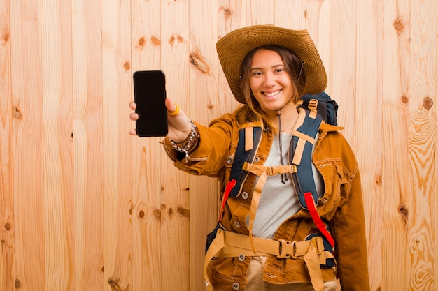 Mujer joven viajero bonita con un teléfono móvil