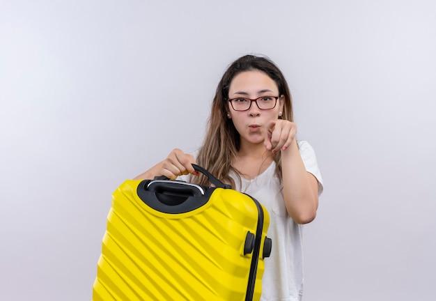 Mujer joven viajero en camiseta blanca con maleta apuntando disgustado en la parte delantera