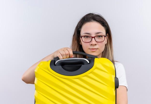 Mujer joven viajero en camiseta blanca con maleta mirando con expresión seria y segura de pie sobre la pared blanca