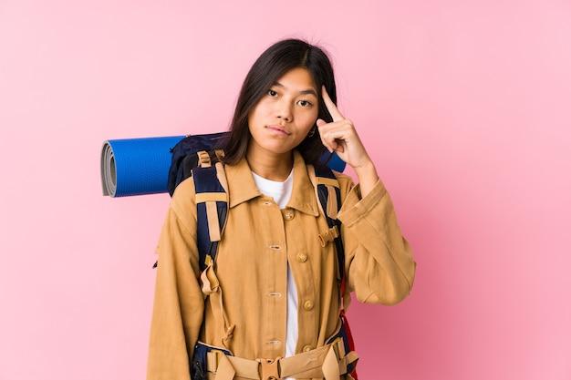 Mujer joven viajero chino aislado señalando el templo con el dedo, pensando, centrado en una tarea.