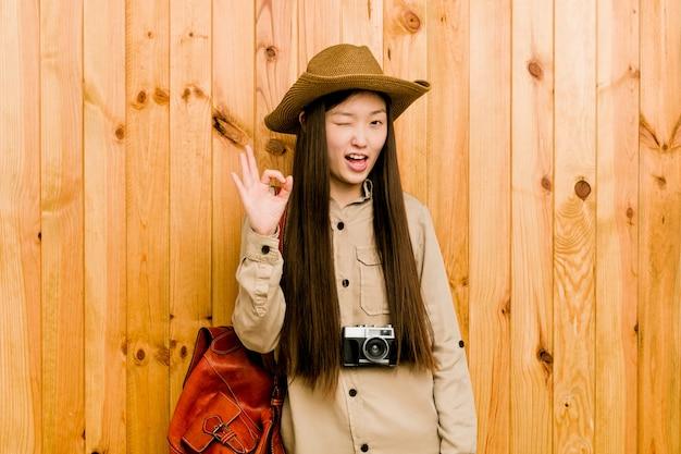 Mujer joven viajero chino guiña un ojo y tiene un gesto bien con la mano.
