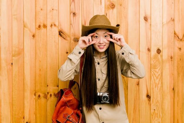 Mujer joven viajero chino manteniendo los ojos abiertos para encontrar una oportunidad de éxito.