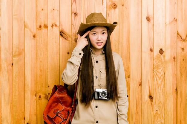 Mujer joven viajero chino que muestra un gesto de decepción con el dedo índice.