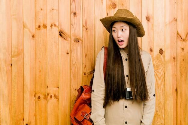 Mujer joven viajero chino sorprendida por algo que ha visto.