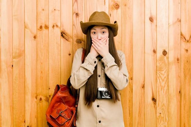 Mujer joven viajero chino sorprendido cubriendo la boca con las manos.