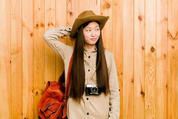 Mujer joven viajero chino tocando la parte posterior de la cabeza, pensando y haciendo una elección.