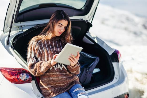 Mujer joven viajero con computadora digital en montañas nevadas en invierno.