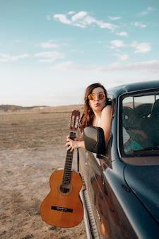 Mujer joven viajero divirtiéndose con la guitarra en el jeep 4x4 haciendo unas vacaciones de pasión por los viajes al atardecer