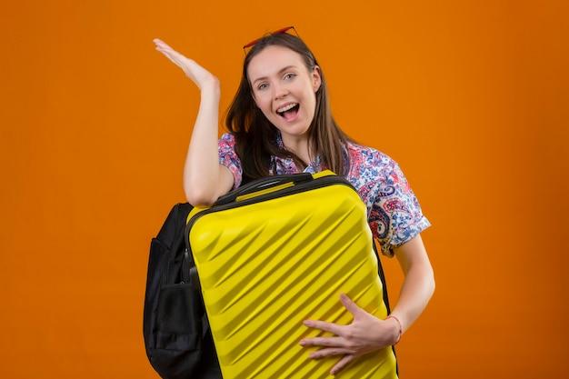 Mujer joven viajero con gafas de sol rojas en la cabeza de pie con mochila sosteniendo la maleta mirando a la cámara y presentando con el brazo de la mano algo sonriendo con cara feliz sobre backg naranja