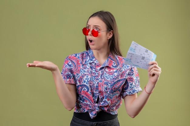 Mujer joven viajero con gafas de sol rojas con entradas mirando decepcionado y sorprendido con el brazo levantado sobre la pared verde