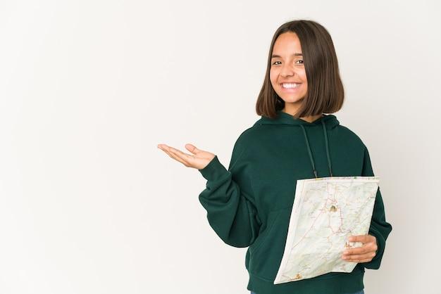 Mujer joven viajero hispano sosteniendo un mapa que muestra un espacio de copia en una palma y sosteniendo otra mano en la cintura.