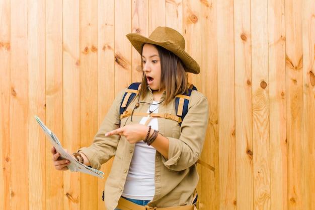 Mujer joven viajero con un mapa contra la pared de madera
