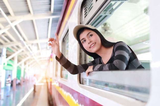 Mujer joven viajero mirando por la ventana