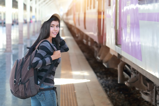 Mujer joven viajero con mochila esperando tren