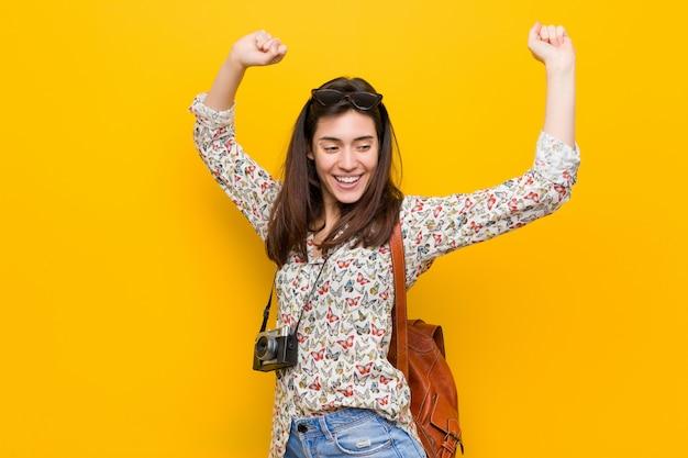 Mujer joven viajero morena celebrando un día especial, salta y levanta los brazos con energía.