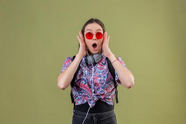 Mujer joven viajero de pie con mochila y auriculares con gafas de sol rojas sorprendido de pie con la boca abierta tocando la cara con las manos sobre fondo verde